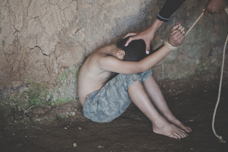 Victim boy with hands tied up with rope in emotional stress and pain,  kidnapped, abused, hostage,  afraid, restricted, trapped, pitiable,  struggle,  Stop violence against children and trafficking Concept. 스톡 콘텐츠 - 119488457