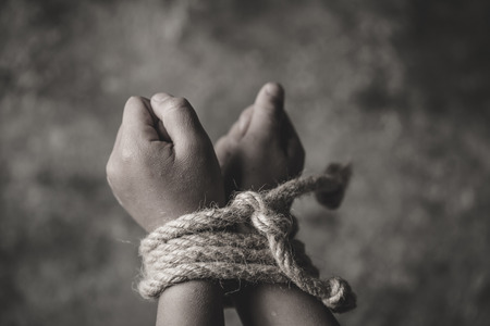 hopeless child hands tied together with rope, human trafficking, Stop abusing violence.