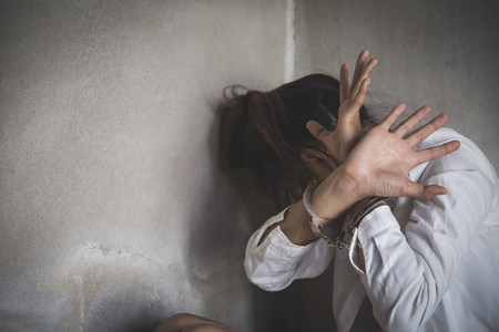 Scared young woman sitting in the corner of her bedroom, despair rape victim waiting for help, Young depressed woman, domestic and rape violence.