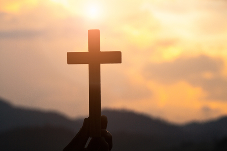 Woman with Wooden cross in hands praying for blessing from god on sunlight background, hope concept - Image