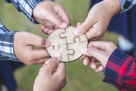 Hands of diverse people assembling jigsaw puzzle, team put pieces together searching for right match, help support in teamwork to find common solution concept, top close up view Stock Photo