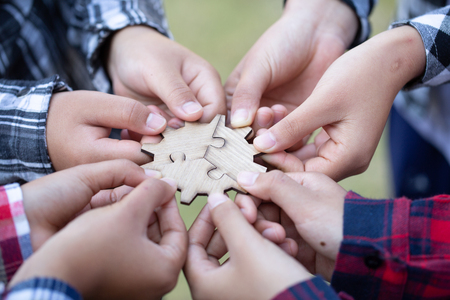 Business people Holding Jigsaw Puzzle, group of business people using a jigsaw puzzle to demonstrate the need to work in the same direction to work fully and effectively