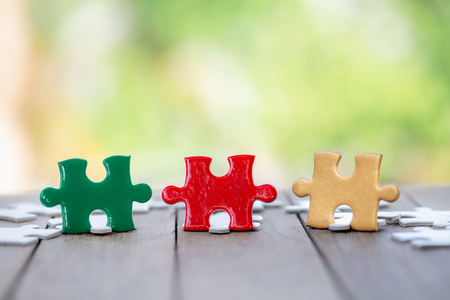 piece of Red green and gold jigsaw puzzle On the old wood. teamwork concept