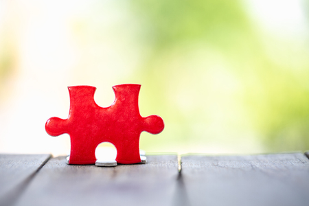 piece of Red  jigsaw puzzle On the old wood And green background. teamwork concept.  symbol of association and connection. business strategy.