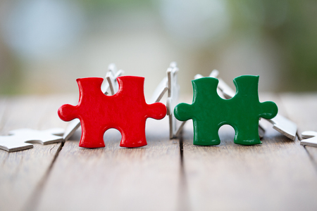 piece of Red and green  jigsaw puzzle On the old wood. teamwork concept.  symbol of association and connection. business strategy. 写真素材