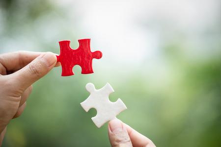 Verbinden Sie weiße und rote Puzzleteile von Hand mit Wortproblemen und Lösungen. Symbol der Assoziation und Verbindung. Geschäftsstrategie. Teamwork-Konzept.