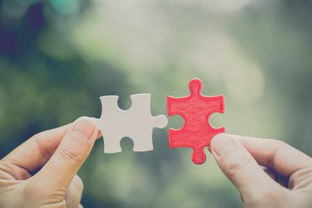 Hand verbindt witte en rode puzzeldelen met woordprobleem & oplossing. symbool van associatie en verbinding. Bedrijfsstrategie. Teamwerkconcept. Stockfoto