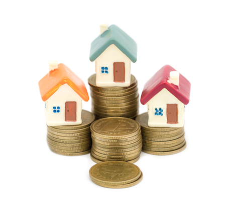 Miniature house on stack coins using as property and business concep, isolated on white background, business house investment ideas concept with coin money stack. Growth of real estate business Reklamní fotografie