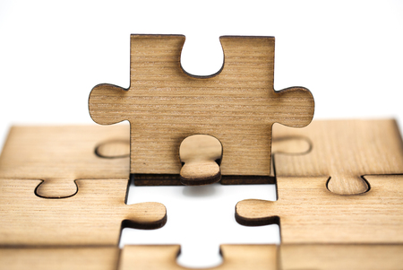 Placing missing a piece of puzzle. business concept, pieces of wooden jigsaw are connected together isolated on white background. concept of connecting.