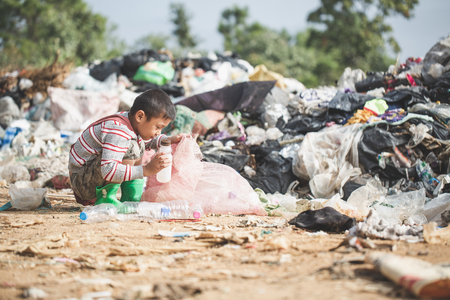 Poor boy collecting garbage in his sack to earn his livelihood, The concept of poor children and poverty Archivio Fotografico