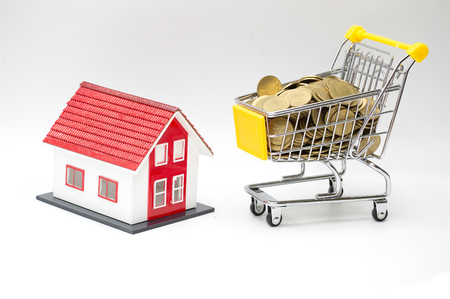 Model red house and coin in shopping cart concept for mortgage saving on white background.