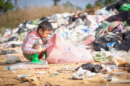 environment Earth Day, Child sitting to separate garbage to be recycled. The concept helps reduce air pollution and protect the environment.