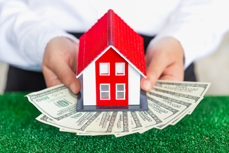 Businessmen holding money and red house models. Real estate loan concept