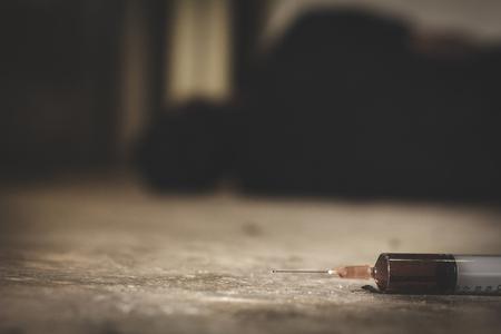 Chico adicto, chico malo - adicto con una jeringa usando drogas en el piso El concepto de antidrogas, sobredosis, drogadicto masculino, jeringa de drogas,