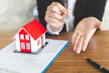 Uw nieuwe huis, makelaar die huissleutel vasthoudt aan zijn klant na ondertekening van de contractovereenkomst op kantoor, concept voor onroerend goed, onroerend goed huren Stockfoto