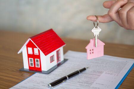 Ihr neues Haus, Immobilienmakler, der nach Unterzeichnung der Vertragsvereinbarung im Amt den Hausschlüssel für seinen Kunden hält, Konzept für Immobilien, Vermietung von Immobilien Standard-Bild