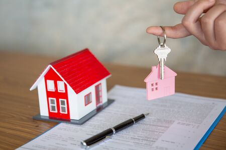Your new house, real estate agent holding house key to his client after signing contract agreement in office,concept for real estate, renting property 스톡 콘텐츠