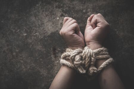 Hands tied up with rope of a missing kidnapped, abused, Violence against children, victim child in pain, human trafficking Concept. Stock Photo