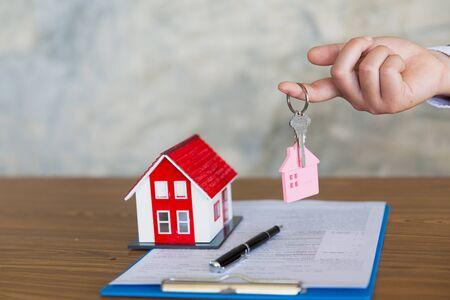 Immobilienmakler hält Hausschlüssel für seinen Kunden nach Unterzeichnung der Vertragsvereinbarung im Amt, Konzept für Immobilien, Vermietung von Immobilien