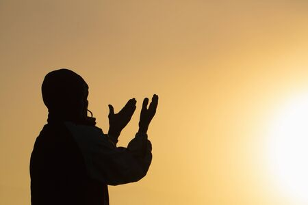 Man praying at sunset mountains raised hands Travel Lifestyle spiritual relaxation emotional concept, Freedom and travel adventure. Banco de Imagens