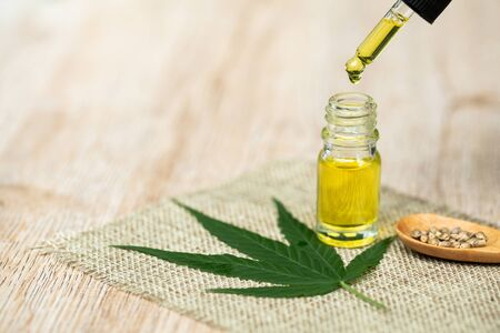 CBD hemp oil, droplet dosing a biological and ecological hemp plant herbal pharmaceutical cbd oil from a jar.