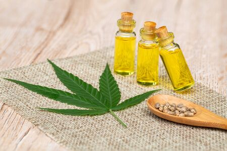 CBD hemp oil  products,  Cannabis oil against Marijuana plant. Herbal Treatment, Alternative Medicine 版權商用圖片