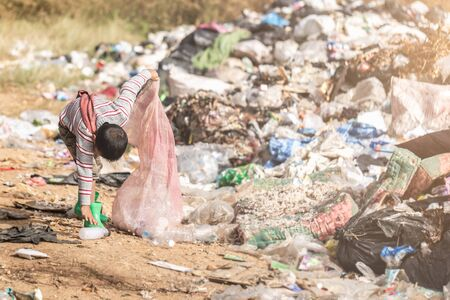Poor children collect and sort waste for sale, concepts of poverty and the environment. Stock Photo