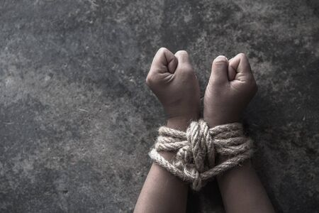 Hands tied up with rope of a missing kidnapped, abused, Violence against children, victim child in pain, human trafficking Concept.