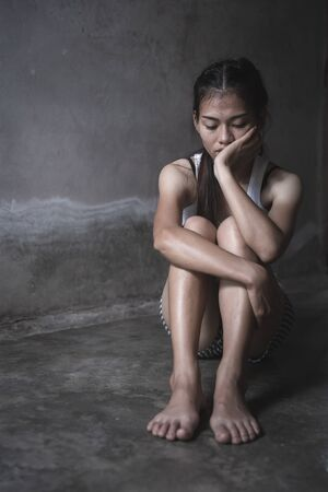 Sad depressed woman suffering and from family life. women sitting in dark room and crying, Young beautiful women thinking how to solve problem, Stop violence against women Stock Photo