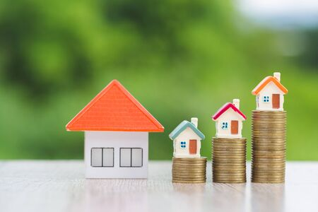 Mini model house on coins stack, growing business, Property investment and house mortgage financial concept isolated on white background