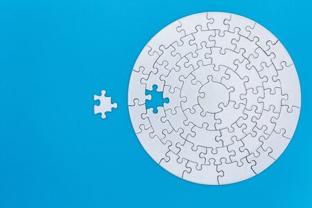 Unfinished white jigsaw puzzle pieces on blue background, The last jigsaw puzzle of success.