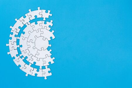 White jigsaw pieces on a blue background, Copy space, Concept image of unfinished task.  missing jigsaw puzzle pieces and business concept with a puzzle piece missing.