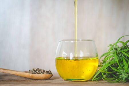 Pouring hemp oil  and hemp seeds in a wooden spoon on a green hemp leaf background, CBD Hemp oil.