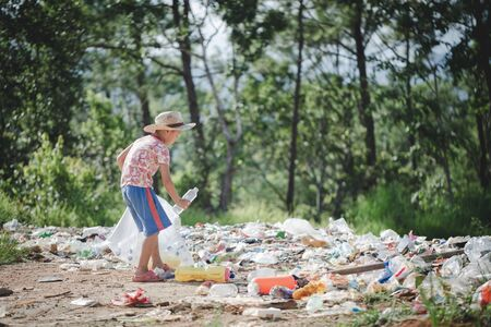 A poor boy collecting garbage waste from a landfill site in the outskirts, the lives and lifestyles of the poor, Child labor, Poverty and Environment Concepts Stock Photo