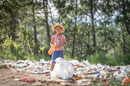 A poor boy collecting garbage waste from a landfill site in the outskirts.  children work at these sites to earn their livelihood. Poverty concept.