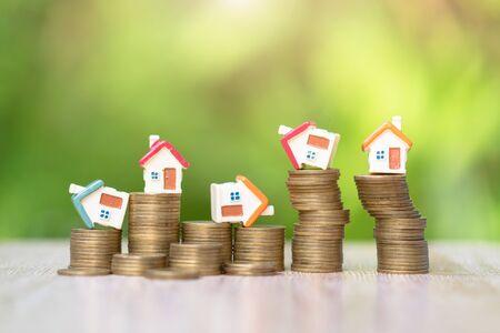 Maison sur pile de pièces, investissement immobilier et hypothèque immobilière. Notion de gestion des risques.
