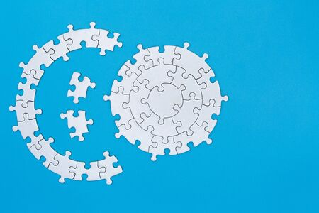 White jigsaw puzzle on blue background, Copy space.