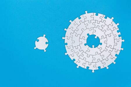 Unfinished white jigsaw puzzle pieces on blue background, The last piece of jigsaw puzzle, Copy space.