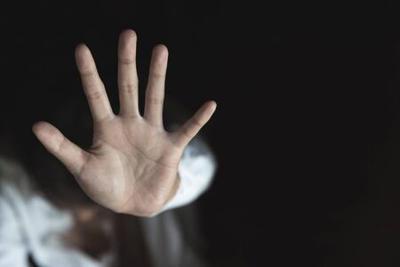 Womans hand extended signaling to stop useful to campaign against violence, gender or sexual discrimination