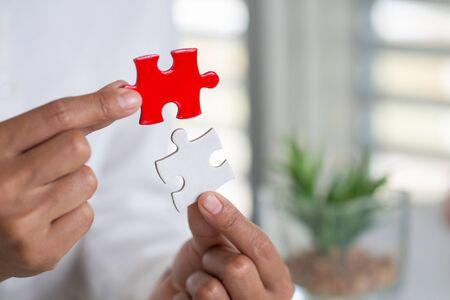 Nahaufnahmehand des Mannes, der Puzzle, Geschäftslösungen, Erfolgs- und Strategiekonzept verbindet