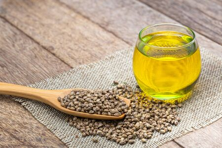 Hemp seeds in wooden spoon and hemp oil in a glass jar on brown wooden table. medical marijuana concept, CBD cannabis OIL. Stock Photo