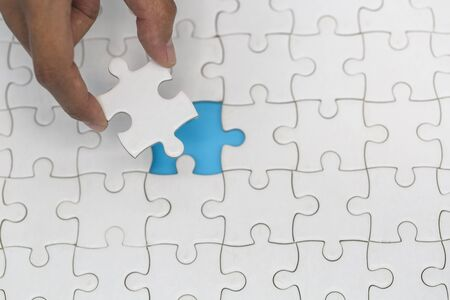 Hand placed the last piece of jigsaw puzzle, conceptual of problem solving, finding a solution Banque d'images