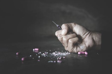 Stop drug addiction concept. A human hand holding a needle for heroin. International Day against Drug Abuse.