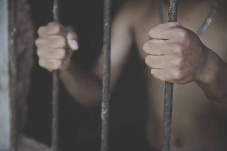 Male prisoners were severely strained in the dark prison, violence, human trafficking,  prison and prisoner concept. Stock fotó