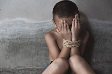 victim child tied up with rope in emotional stress and pain. Stop abusing boy violence, human trafficking, Human Rights Day Reklamní fotografie