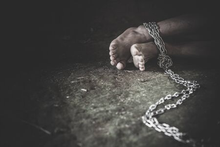 Hopeless man foot tied together with chain, Victims of human trafficking 版權商用圖片
