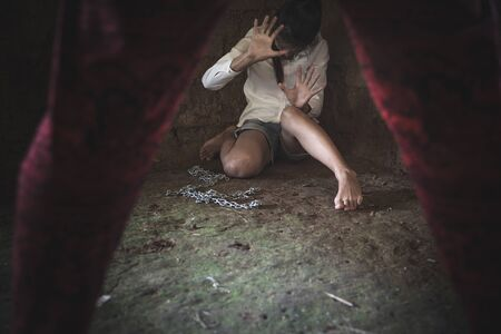 A man standing and holding a chain in his hand, was about to attack a woman sitting in the corner of a dark room.Violence against women, Human rights violations, Human trafficking. Stock Photo