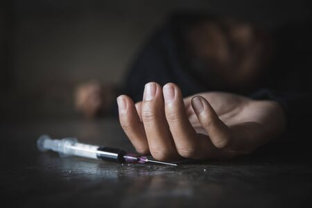 Human hand of a drug addict and a syringe with narcotic syringe lying on the floor. Anti drug concept.