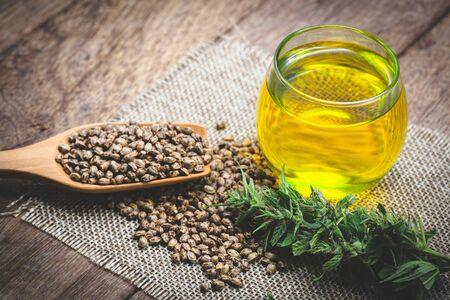 Cannabissamen und CBD-Öl-Cannabisextrakt, grüner Hanfblatthintergrund, medizinisches Cannabiskonzept.