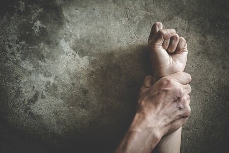 Close up of man hands holding a woman hands for rape and sexual abuse, anti-trafficking and stopping violence against women, International Women's Day Foto de archivo